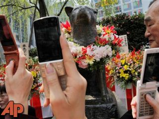 "People take photos of a bronze statue of Japanese Akita dog ""Hachi"" during the 74th memorial service for the dog, intimately called Hachiko, in front of Shibuya railway station in Tokyo. (AP Photo/Itsuo Inouye, FILE)"