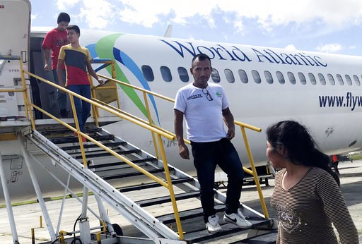 (AP Photo/Colleen Long). Fourteen-year-old Hermelindo Juarez, second from left, looks around at his home country, Tuesday, July 10, 2018, as he and his father, Deivin Juarez, left, step off a chartered flight from the U.S. in Guatemala City, Guatemala,...