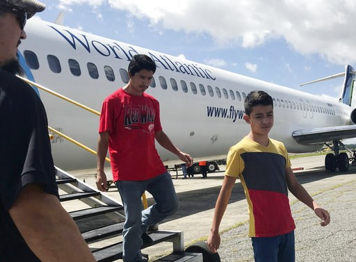 (AP Photo/Colleen Long). Fourteen-year-old Hermelindo Juarez, right, and his father, Deivin Juarez, step off a chartered flight from the U.S., Tuesday, July 10, 2018 in Guatemala City, Guatemala, after the two were deported. They were separated for wee...