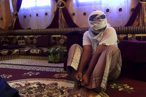 (AP Photo/Maad El Zikry, File). FILE -- In this May 11, 2017 file photo, a former detainee covers his face for fear of being detained again, as he shows how he was kept in handcuffs and leg shackles while held in a secret prison at Riyan airport in the...