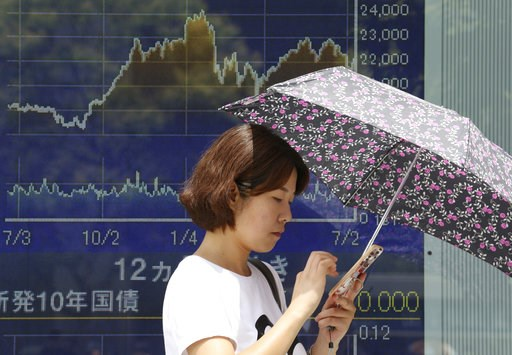 (AP Photo/Koji Sasahara). In this Wednesday, July 11, 2018, photo, a woman stands in front of an electronic stock board of a securities firm in Tokyo. Asian stock markets rose Thursday, July 12, 2018, following Wall Street's decline amid U.S.-Chinese t...