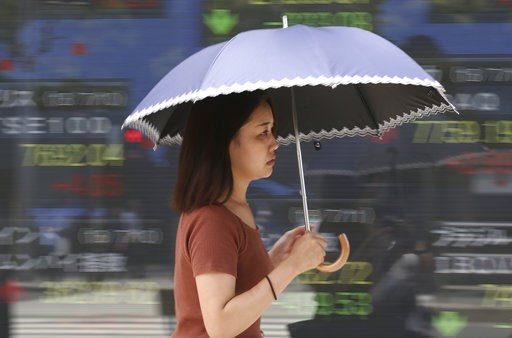(AP Photo/Koji Sasahara). In this Wednesday, July 11, 2018, photo, a woman walks by an electronic stock board of a securities firm in Tokyo. Asian stock markets rose Thursday, July 12, 2018, following Wall Street's decline amid U.S.-Chinese trade tensi...