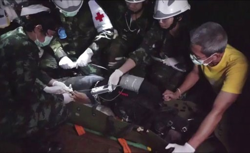 (Thai NavySEAL Facebook Page via AP). This undated photo from video released via the Thai NavySEAL Facebook Page on Wednesday, July 11, 2018, shows rescuers hold an evacuated boy inside the Tham Luang Nang Non cave in Mae Sai, Chiang Rai province, in n...