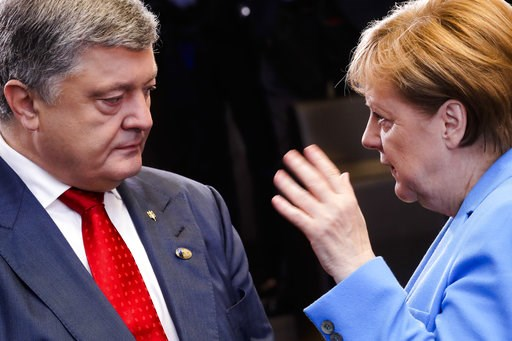 (AP Photo/Markus Schreiber). German Chancellor Angela Merkel, right, and Ukraine's President Petro Poroshenko, left, talk together, prior to a working session during a summit of heads of state and government at NATO headquarters in Brussels on Wednesda...
