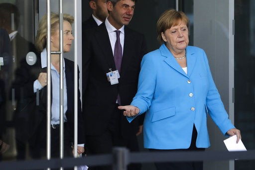 (AP Photo/Markus Schreiber). German Chancellor Angela Merkel, right, arrives for a statement with Defense Minister Ursula von der Leyen, left, after a summit of heads of state and government at NATO headquarters in Brussels on Wednesday, July 11, 2018.