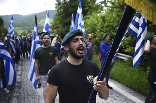 (AP Photo/Giannis Papanikos, file). FILE - In this Sunday, June 17, 2018 file photo, opponents of the deal between Greece and Macedonia on the latter country's new name - North Macedonia - hold Greek flags as they protest at the village of Pisoderi, in...