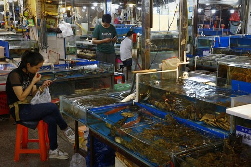"""(AP Photo/Andy Wong). Vendors browse their smartphones at the Jingshen seafood market in Beijing, Thursday, July 12, 2018. China's government vowed on Wednesday to take """"firm and forceful measures"""" as the U.S. threatened to expand tariffs to thousands ..."""