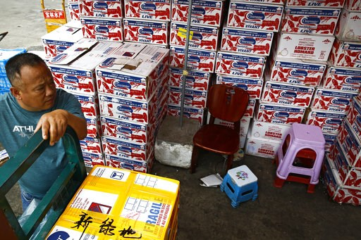 """(AP Photo/Andy Wong). A man waits for the goods to be load on his tricycle at a dealer selling imported seafoods at the Jingshen seafood market in Beijing, Thursday, July 12, 2018. China's government vowed on Wednesday to take """"firm and forceful measur..."""