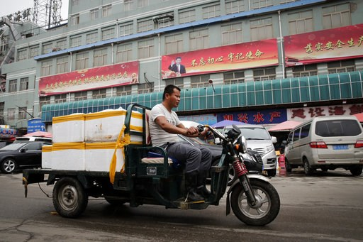 (AP Photo/Andy Wong). A man rides a motor-tricycle loaded with seafood products past by a billboard featuring Chinese President Xi Jinping and the government propaganda on display at the Jingshen seafood market in Beijing, Thursday, July 12, 2018. Chin...