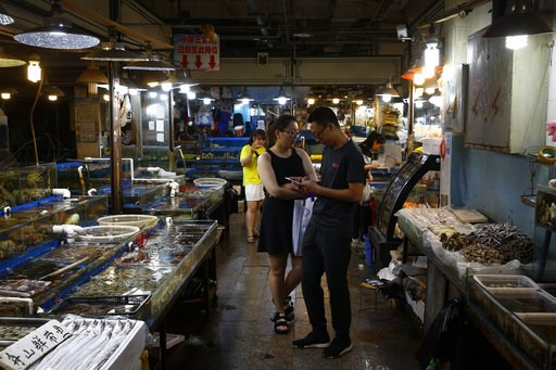 """(AP Photo/Andy Wong). A Chinese couple shop for seafoods at the Jingshen seafood market in Beijing, Thursday, July 12, 2018. China's government vowed on Wednesday to take """"firm and forceful measures"""" as the U.S. threatened to expand tariffs to thousand..."""
