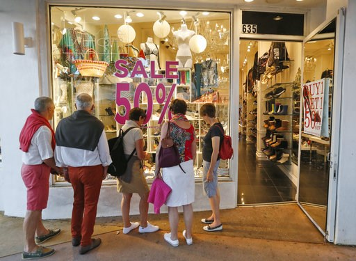 (AP Photo/Wilfredo Lee, File). FILE- In this April 26, 2017, file photo, window shoppers look into a store on Miami Beach, Florida's Lincoln Road. As Amazon gears up for its Prime Day promotion, other big-name retailers like Macy's and eBay are launchi...