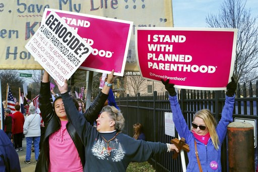 (AP Photo/Jim Salter, File). FILE - In this Feb. 11, 2017, file photo, a Planned Parenthood supporter and opponent try to block each other's signs during a protest and counter-protest of abortion in St. Louis. If a Supreme Court majority shaped by Pres...