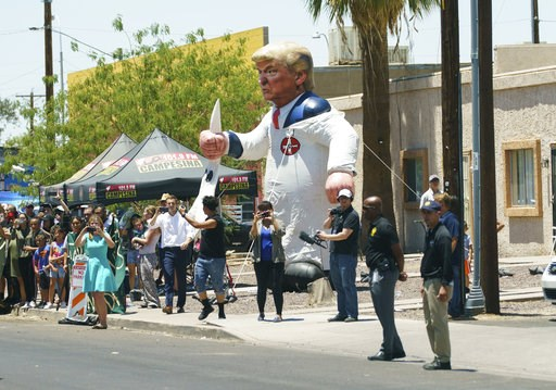 (AP Photo/Carolyn Kaster). Protesters place a large inflatable balloon in the likeness of President Donald Trump dressed in a Ku Klux Klan sheet across the street from Southwest Key Campbell, a shelter for children that have been separated from their p...