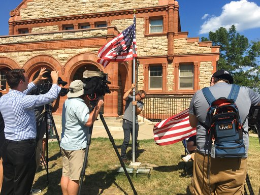 (Kim Callahan/The Journal-World via AP). A KU employee takes down an altered American flag in a public art display in front of KU's Spooner Hall in Lawrence, Kan., Wednesday, July 11, 2018. A controversial art display that included an altered U.S. flag...