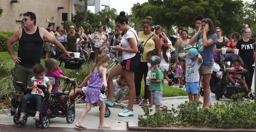 (Carline Jean/South Florida Sun-Sentinel via AP). Parents and kids wait in line for close to an hour at Coral Square mall in Coral Springs, Fla., for the Build-A-Bear Workshop Pay Your Age day event, Thursday, July 12, 2018. Customers were allowed cust...