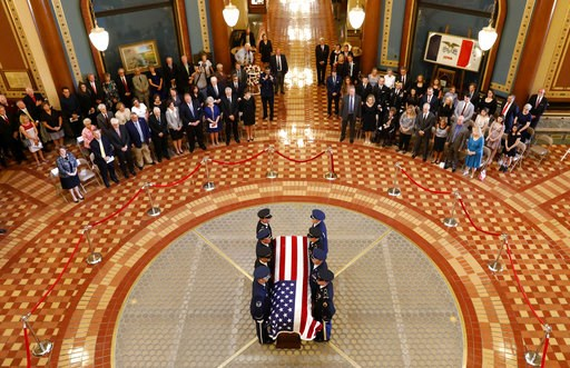 (AP Photo/Charlie Neibergall). Honor Guard members stand over the casket of former Iowa Gov. Robert Ray during a memorial service, Thursday, July 12, 2018, at the Statehouse in Des Moines, Iowa.