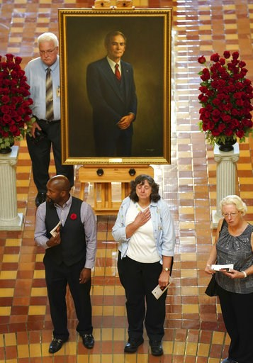 (AP Photo/Charlie Neibergall). Mourners stand in front of a portrait of former Iowa Gov. Robert Ray during a memorial ceremony, Thursday, July 12, 2018, at the Statehouse in Des Moines, Iowa.