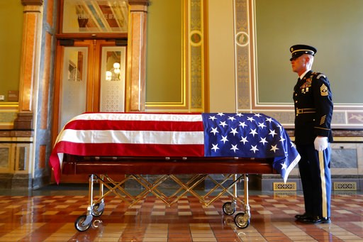 (AP Photo/Charlie Neibergall). An Honor Guard member stands next to the casket of former Iowa Gov. Robert Ray before before a ceremony, Thursday, July 12, 2018, at the Statehouse in Des Moines, Iowa.