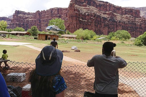 (Benji Xie via AP). This Thursday, July 12, 2018 photo released by Benji Xie shows a helicopter landing to rescue people from flooding on the Havasupai reservation in Supai, Ariz. Rescue workers were evacuating about 200 tourists Thursday who were caug...