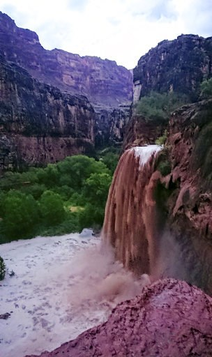 (Benji Xie via AP). This Wednesday, July 11, 2018 photo released by Benji Xie shows flooding from a waterfall on the Havasupai reservation in Supai, Ariz. About 200 tourists were being evacuated Thursday from a campground on tribal land near famous wat...
