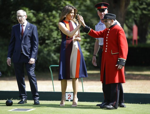 "(AP Photo/Luca Bruno, Pool). U.S. First Lady Melania Trump high-fives with a British military veteran known as a ""Chelsea Pensioner"" during a game of bowls with Philip May, the husband of British Prime Minister Theresa May, at The Royal Hospital Chelse..."