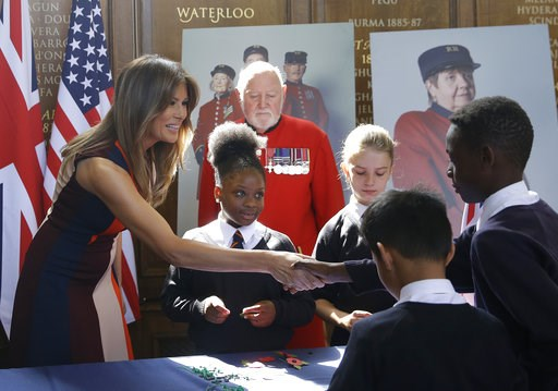 "(AP Photo/Luca Bruno, Pool). U.S. First Lady Melania Trump shakes hands with a schoolboy as she helps children to make poppies as she meets British military veterans known as ""Chelsea Pensioners"" at The Royal Hospital Chelsea in central London Friday, ..."