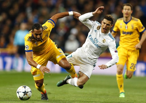(AP Photo/Francisco Seco). FILE - In this Wednesday, April 11, 2018 file photo Real Madrid's Cristiano Ronaldo is tackled by Juventus' Medhi Benatia during a Champions League quarter final second leg soccer match between Real Madrid and Juventus at the...