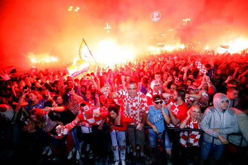 (AP Photo/Nikola Solic, File). FILE - In this July 11, 2018 file photo, Croatian fans cheer while watching the semifinal match between Croatia and England at the 2018 soccer World Cup, in Zagreb, Croatia. In the Balkans, even soccer is political, so it...