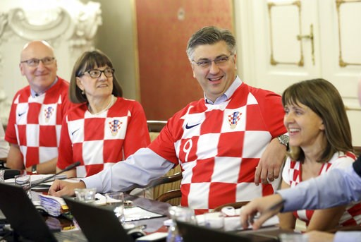 (AP Photo). Croatia's Prime Minister Andrej Plenkovic, center, sits between ministers wearing Croatian national soccer team jerseys during during a government session in Zagreb, Croatia, Thursday, July 12, 2018, a day after Croatia qualified in finals ...