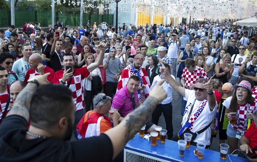(AP Photo/Pavel Golovkin). Croatia's soccer fans cheer as they meet in Nikolskaya street near the Kremlin in Moscow, Russia, Friday, July 13, 2018.
