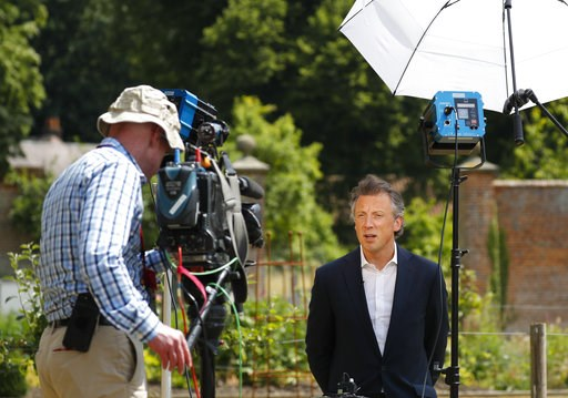 (AP Photo/Pablo Martinez Monsivais). Tom Newton Dunn, Political Editor of the Sun Newspaper, right, is seen speaking to Fox Television News network at Chequers, in Buckinghamshire, England, Friday, July 13, 2018. In an interview with Sun newspaper, Pre...