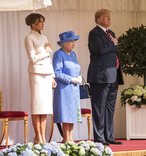 (Richard Pohle/Pool Photo via AP). Britain's Queen Elizabeth II, centre stands with US President Donald Trump and first lady Melania on the dias in the Quadrangle as they listen to the US national anthem, during a ceremonial welcome at Windsor Castle, ...
