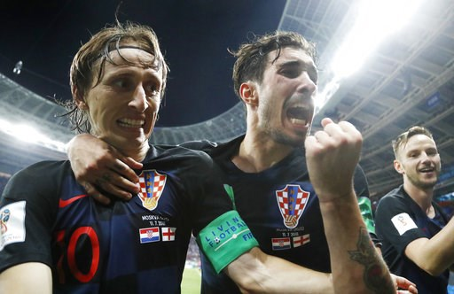 (AP Photo/Frank Augstein). Croatia's Luka Modric, left, Sime Vrsaljko and Ivan Rakitic, right, celebrate after Croatia's Mario Mandzukic scored his side's second goal during the semifinal match between Croatia and England at the 2018 soccer World Cup i...