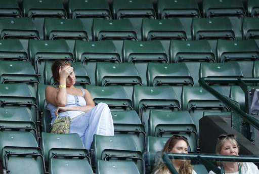 (AP Photo/Ben Curtis). Spectators attend the men's singles quarterfinal tennis match between John Isner of the United States and Canada's Milos Raonic, at the Wimbledon Tennis Championships, in London, Wednesday July 11, 2018.