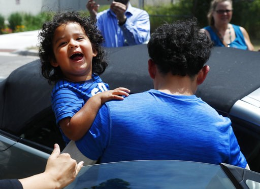 (AP Photo/Paul Sancya, File). FILE - In this July 10, 2018, file photo, Ever Reyes Mejia, of Honduras, carries his son to a vehicle after being reunited and released by United States Immigration and Customs Enforcement in Grand Rapids, Mich. With one d...