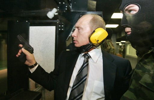 (Dmitry Astakhov, Sputnik, Kremlin Pool Photo via AP). FILE In this file photo taken on Wednesday, Nov. 8, 2006, President Vladimir Putin wears headphones as he tests a pistol in a shooting range as he visits the Defense Ministry's Main Intelligence Di...