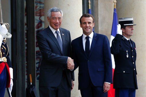 (AP Photo/Thibault Camus). France's President Emmanuel Macron, right, shakes hand with Singapore Prime Minister Lee Hsien Loong, prior to a State dinner, at the Elysee Palace, in Paris, Friday, July 13, 2018.