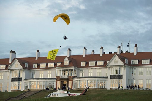 """( John Linton/PA via AP). In this Friday, July 13, 2018 photo, a Greenpeace protester flying a microlight passes over US President's Donald Trump's resort in Turnberry, South Ayrshire, Scotland with a banner reading """"Trump: Well Below Par"""", shortly aft..."""