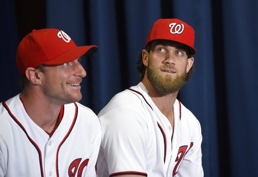(AP Photo/Nick Wass, File). FILE - In this July 26, 2017, file photo, Washington Nationals' Max Scherzer, left, and Bryce Harper look on at a baseball press conference to unveil the 2018 MLB All-Star Game logo, in Washington. Thirteen years after Major...