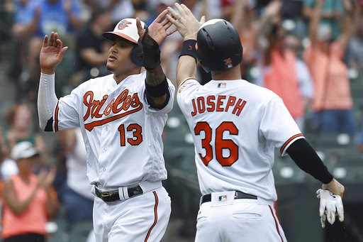 (AP Photo/Gail Burton). Baltimore Orioles' Manny Machado, left, and Caleb Joseph score against the Texas Rangers in the third inning of a baseball game, Sunday, July 15, 2018, in Baltimore.