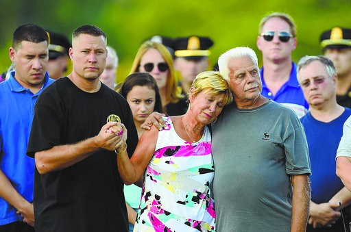 (Christopher Evans/The Boston Herald via AP). Members of the Chesna family, from left, Michael's brother Eric, his mother Maryann and father Chuckie, support each other during a vigil for slain Weymouth Police Officer Michael Chesna and an innocent bys...