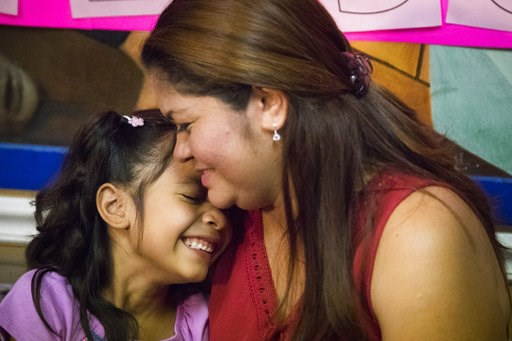 (Marie D. De Jes's/Houston Chronicle via AP, File). FILE - In this July 13, 2018, file photo, Allison, 6, and her mother Cindy Madrid share a moment during a news conference in Houston, where the mother and daughter spoke about the month and one day th...