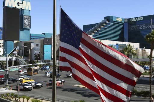 (AP Photo/Ronda Churchill, File). FILE - In this Oct. 2, 2017 file photo, an American flag waves near a police barricade on the Las Vegas Strip with the MGM Grand hotel and casino in the background after a mass shooting in Las Vegas. The unprecedented ...
