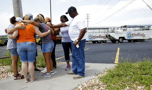 (AP Photo/Charlie Riedel). People pray outside Ride the Ducks, an amphibious tour operator involved in a boating accident on Table Rock Lake, Friday, July 20, 2018 in Branson, Mo.