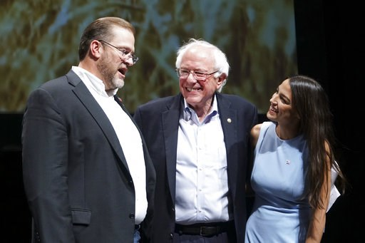 (Jaime Green/The Wichita Eagle via AP). Kansas congressional candidate James Thompson, left, U.S Sen. Bernie Sanders, I-Vt.,  and Alexandria Ocasio-Cortez, a Democratic congressional candidate from New York, stand together on stage after a rally, Frida...