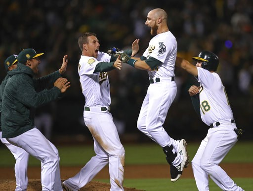 (AP Photo/Ben Margot). Oakland Athletics' Jonathan Lucroy, second from right, celebrates with Chad Pinder (18) and Stephen Piscotty, second from left, after driving in the winning run against the San Francisco Giants in the 11th inning of a baseball ga...