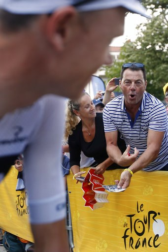 (AP Photo/Christophe Ena ). A man makes a gesture of injecting himself as he he shows his disapproval of Britain's Chris Froome, left, prior to the fifteenth stage of the Tour de France cycling race over 181.5 kilometers (112.8 miles) with start in Mil...