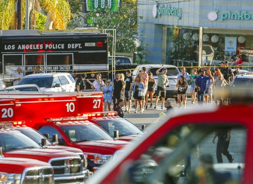 (AP Photo/Damian Dovarganes). Los Angeles Police SWAT officers escort a group of people who were held for their safety by police across businesses surrounding a Trader Joe's supermarket, after a gunman held dozens of people hostage inside the store bef...