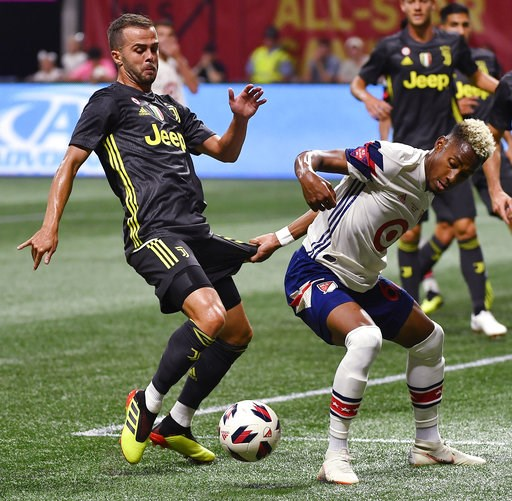 (AP Photo/Mike Stewart). MLS All-Star defender Michael Amir Murillo, right, holds the shorts of Juventus midfielder Miralem Pjanic (5) during the MLS All-Star soccer match, Wednesday, Aug. 1, 2018, in Atlanta.