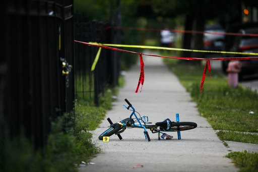 (Armando L. Sanchez/Chicago Tribune via AP). In this Sunday, Aug. 5, 2018 photo, evidence markers sit on the ground at the scene where a boy was killed after being shot in the abdomen while riding his bike in Chicago. Police Superintendent Eddie Johnso...